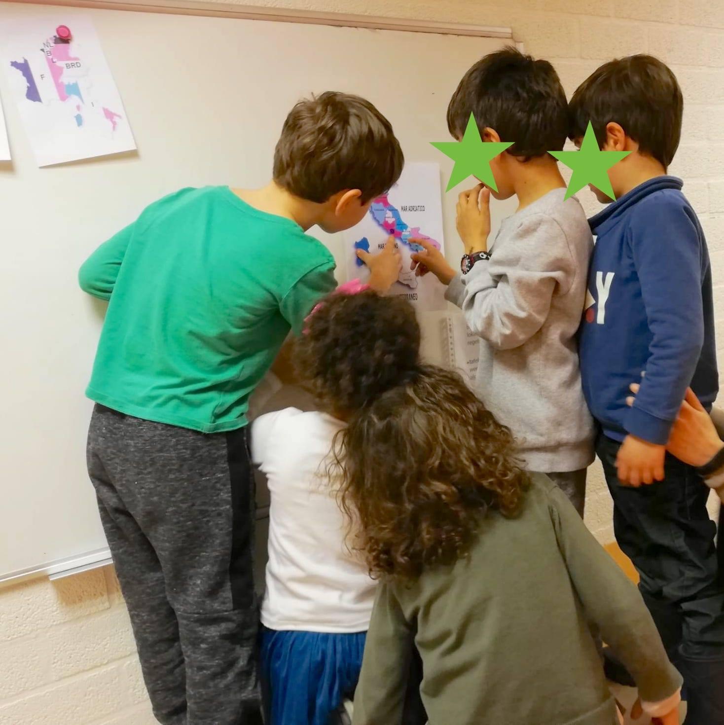 bambini che guardnao una mappa dell'Italia