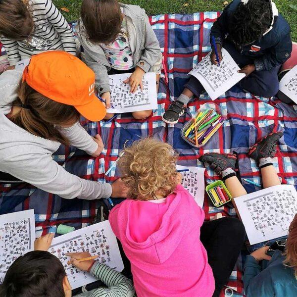 bambini disegnano con insegnante al parco