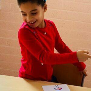 bambina sorride guardando un disegno
