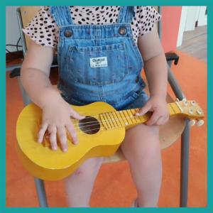 bambina con ukulele durante il corso di musica