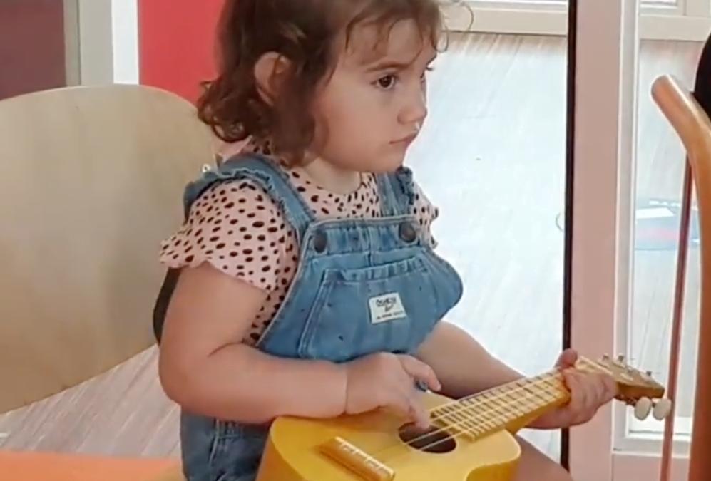 bambina suona un ukulele